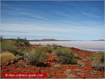 salt lake surrounded by red hills
