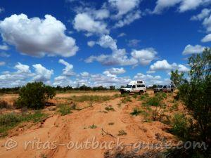 A colourful Outback landscape with a campervan and a car