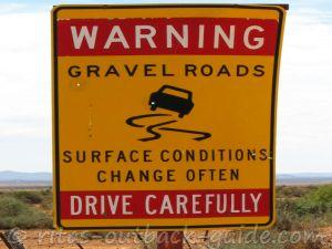 A warning road sign that says gravel road ahead