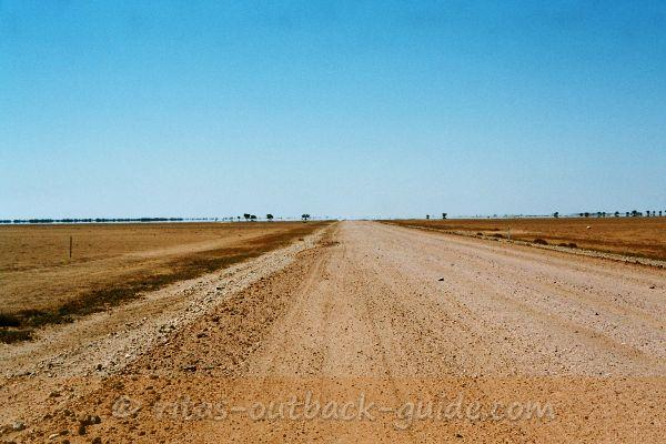 a flat and sandy road with mirages on the horizon