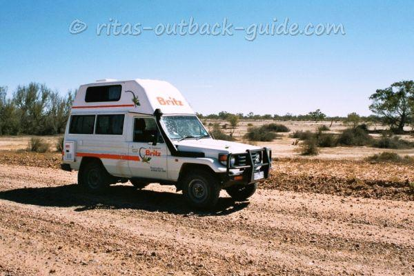 An outback campervan crossing the dry bed of Cooper Creek