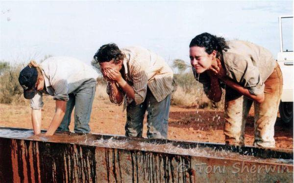 Young women wash themselves in a cattle watering tank