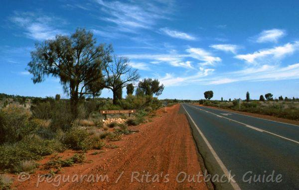 Outback road in Central Australia, bitumen in lined by red earth