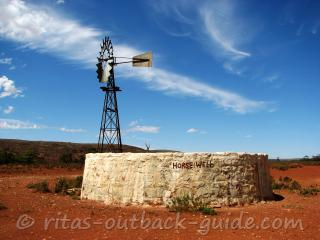 A windmill and stone well