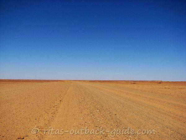A wide empty dirt road in the Outback
