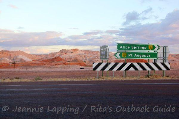 The rugged mole hills around Coober Pedy and a road sign on the Stuart Highway